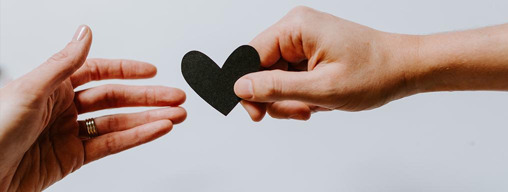 due mani si passano un cuore di carta