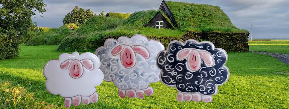 Pecore disegnate su una fotografia ritraente una casa in torba