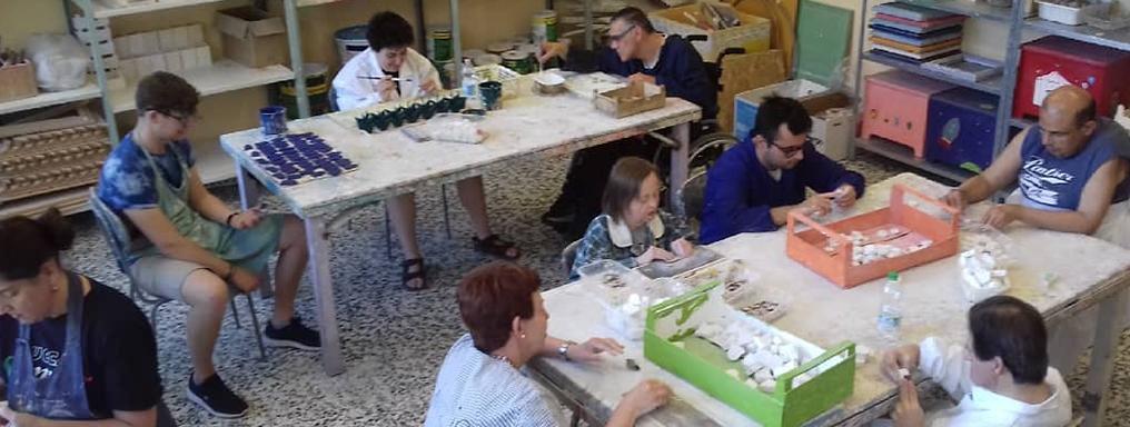 Un gruppo di ragazzi con disabilità lavora a prodotti in legno e ceramica